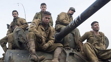 The cast of Fury assembled upon a tank