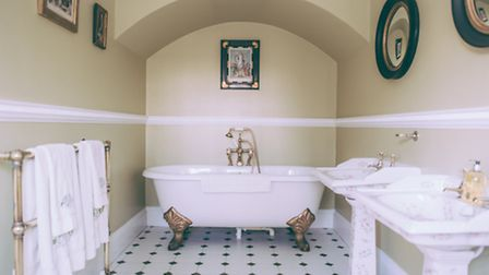 The en-suite bathroom in the Mulberry Room with Colefax wallpaper and a freestanding, roll top bath