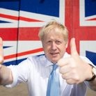 Boris Johnson poses for a 2019 photograph in front of a Union flag