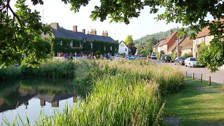 The pond in the heart of the village with The Greyhound Inn behind