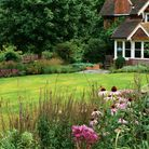 Swathes of lawn contrast with billowing flower beds