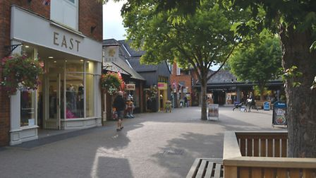Furlong Centre with smart shops, pavement cafes and colourful hanging baskets