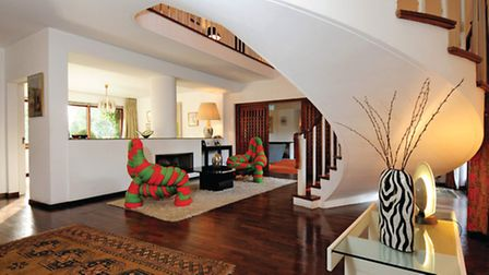 The distinctive pair of padded red and green chairs either side of the fireplace in the hall are by