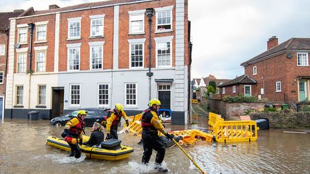 Fire and Rescue officers use an inflatable raft to rescue a woman in Bewdley, Worcestershire. Photo: