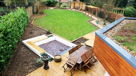 The landscaped rear garden awaiting planting. On the left is a fire pit and on the right a living ro