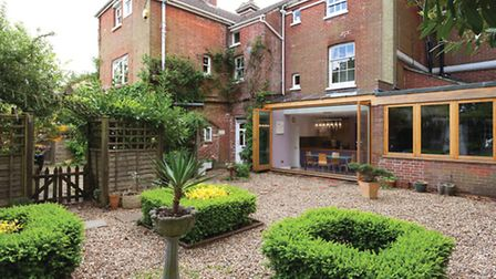 The back of Bembridge House with bifold doors opening up the kitchen to private garden 'rooms'