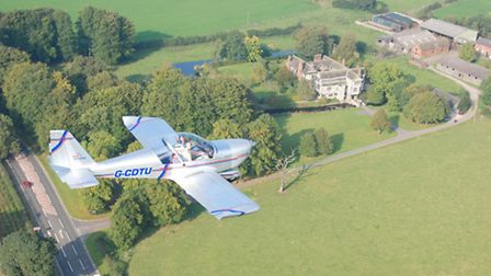 A fixed wing Eurostar microlight over Little Moreton Hall