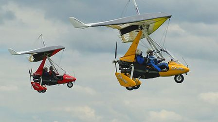 Two flexwing microlights in the air above Cheshire