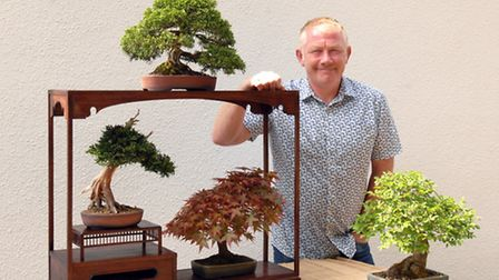 Simon Jones with a collection of Shohin Bonsai: (from top clockwise) Juniper, Elm, Acer and Yew.