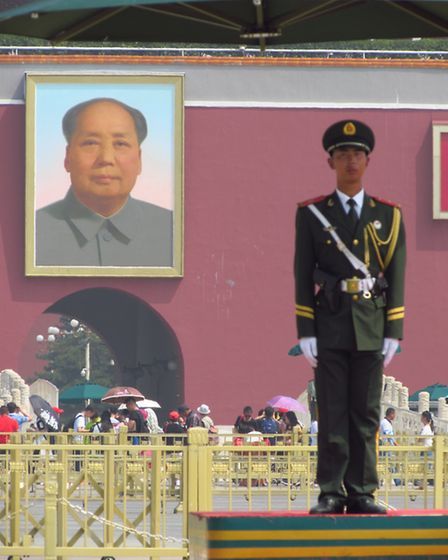 A soldier does guard duty for three hours in Tiananmen Square, the image of Mao Tse-tung behind him