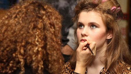 A model has her make up applied as she prepares for the show