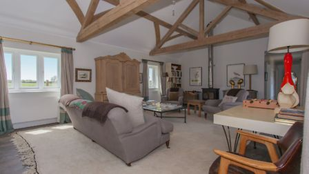 Comfortable sitting room with exposed beams, woodburning stove, warm rugs and deep sofas