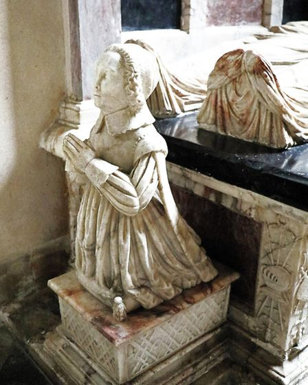 Figure of a girl kneeling at the feet of monument to her parents Sir William and Lady Harrington at