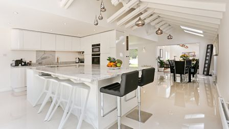 The sleek kitchen flows to the dining room and on to the sitting or 'chatting' room