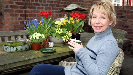 Joanne sitting with a coffee showing how grouped spring plants can be potted up to sit on a garden t