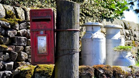Milk churns still part of the rural scene in a village in the Yorkshire Dales, 2014