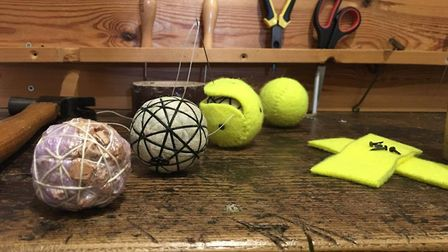 The process of making the balls, which have a solid cork core wound with woven tape and string and c