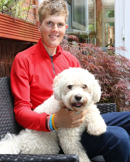 Alex relaxes with, Hector the dog, back at home in Kelsall