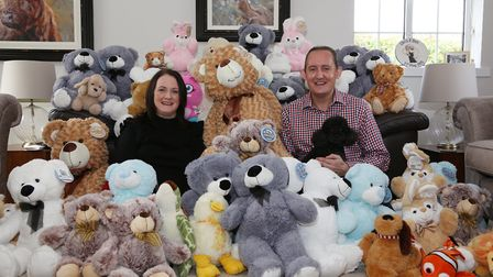 Dee and Chris Drake with Oscar the dog surrounded by a selection of the teddies