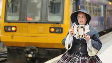 'Elizabeth Gaskell' consults the Discover Amazing Women by Rail booklet at Manchester Piccadilly Sta