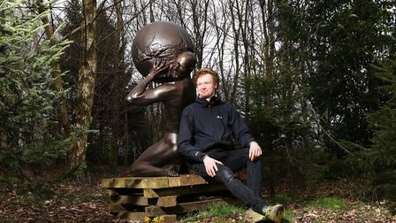 Jago Hartland with his favorite sculpture Atlas by Pete Tatham, in the family run sculpture park (c)