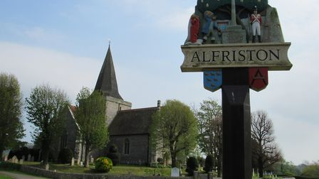 Alfriston village sign with St Andrew's Church in the background