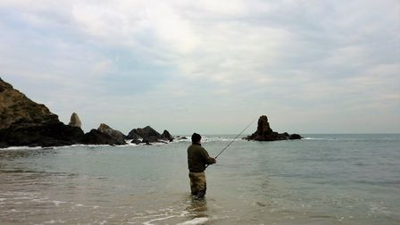 A client fishes for sea bass under Marc's instruction
