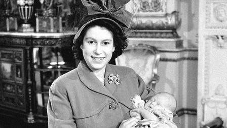 Princess Elizabeth holds her baby son, Prince Charles, after his christening ceremony at Buckingham