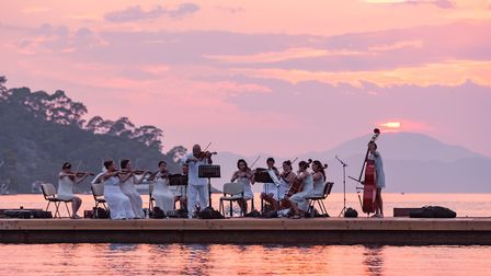 The Ankara Chamber Orchestra perform on a floating pontoon as the sun sets over the Aegean Sea