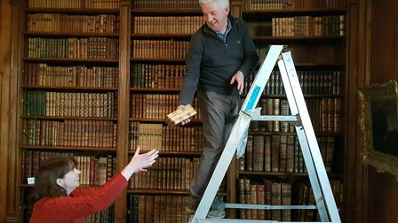 Volunteers begin the long task of removing each book in the library, ready for cleaning