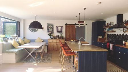 The open plan kitchen and dining area opens to the garden thanks to an expanse of bifold windows and