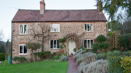 The Waldrons' charming cottage looks like a doll's house with its central front door. The front sect