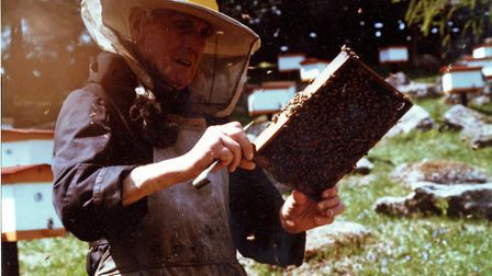 Brother Adam Kehrle, legendary keeper of the Abbey's bees, inspecting the hives