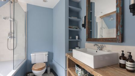The 'Garter Blue' bathroom walls are in an Edward Bulmer paint. The bath, towel rail and other fitti