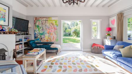 The sitting room is a riot of colour with Orla Kiely Stem rug, shocking pink lampshade, mother-in-la