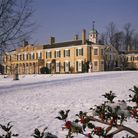 Polesden Lacey in the snow, green shutters against pale yellow exterior. Holly is pictured in the fo