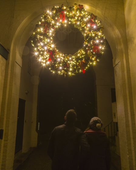 Visitors admiring a giant Christmas wreath hanging from an archway at Polesden Lacey, Surrey.