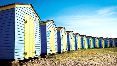 Colourful beach huts hug the coast (c) Getty Images/iStockphoto/Martin Parratt