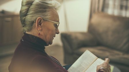 The book is there to fulfill your free time. Senior woman reading book at home. Close up.