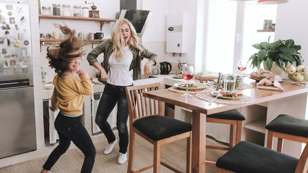 Full length portrait of charming blond woman spending time with her adorable kid. They dancing and l