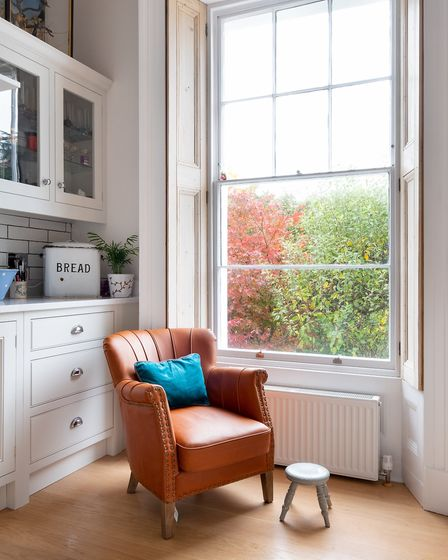The tan leather armchair supplies a splash of colour against the neutral tones of the cabinetry