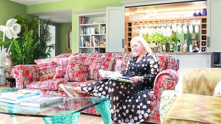 Holly relaxes in her garden room. The glass table is by American artist Danny Lane.