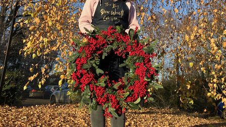 The scarlet winter berries on this wreath will brighten any doorway. Photo: Henry Harrison