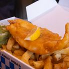 A plate of fish and potato chips in traditional English meal