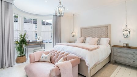 Master bedroom with deeply luxurious bed (from Harrods, no less), buttoned sofa in boudoir pink and