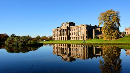 Autumn in the grounds of Lyme Park. The south facade of the Grade I listed building reflecting in th