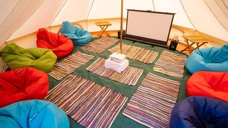 Bell tents can be kitted out with comfortable furniture and a projector screen for up to 10 people.