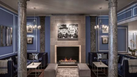 A Paul Wright portrait of Sir Winston and Clementine sits above the fireplce in the hotel lobby. Ima