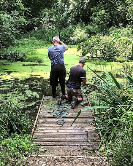Richard Lillicrap and Richard Mottram clearing debris from the pond. Photo: Ray Morton