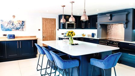 Dark tones of charcoal and blue are lifted by copper accessories in the brand new kitchen. The paint